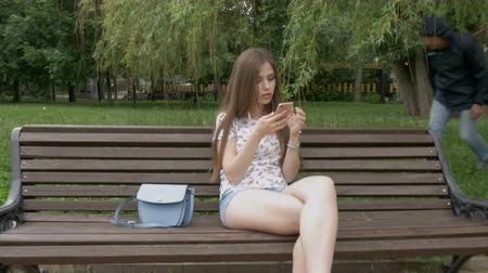 кража : A young beautiful girl does not know that her wallet was stolen. She listens to music on the smartphone. The thief stole the purse from the bag. Close-up Стоковые видеозаписи