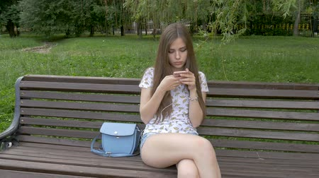 anlamı : Young beautiful girl is sitting on a park bench, looking sms on a smartphone. She got bad news from my boyfriend. Sadness and sadness.