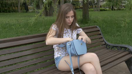 кража : A young girl opens her bag and sees that the thief stole her purse. They will check their things and are very sad about the loss. Sad news.