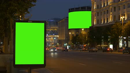 publicity : Two billboards with a green screen. In the evening, on a busy street.