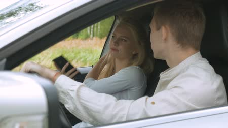 descontente : A blonde girl and her boyfriend are arguing, sitting in the car. Irritation and quarrel.