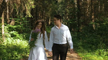 vőlegény : The bride in a white dress and her fianc are strolling through the forest. Stock mozgókép