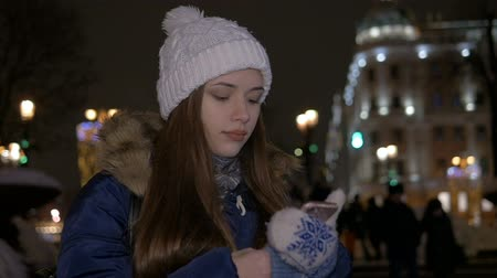 mittens : A girl in a white hat, in winter, walks down the street and reads a message on the smartphone.