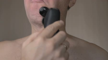 cortiça : The man shaves his face with an electric razor. It is very much covered with bristles. Closeup. slow motion