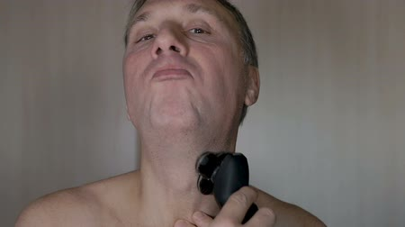 hand on chin : A man shaves his face, a modern electric razor. Slow motion. Very much overgrown with bristles. Stock Footage