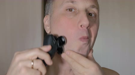 zęby : The man is shaving his face cleanly with an electric razor. Closeup. Wideo