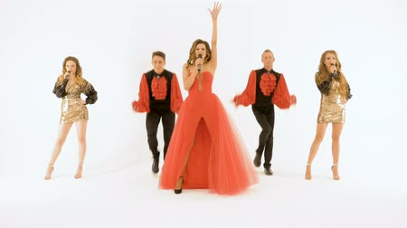 певец : Beautiful singer in a red dress, singing and dancing in the studio on a white background. Стоковые видеозаписи