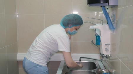 sanitize : A female surgeon is getting ready for surgery. She washes her hands in a special place.