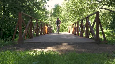 montanhoso : A man is riding a bicycle across the bridge in the park. slow motion