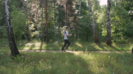 stopy : Male athlete, leads a healthy lifestyle. He runs in the park on a summer day. Dostupné videozáznamy
