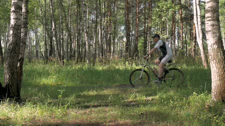 empurrando : The athlete rides a bicycle through the forest on a beautiful sunny day. Excellent mood and good health.