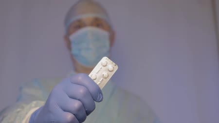 tudós : A doctor surgeon shows the tablets in the package that need to take to a patient after surgery.