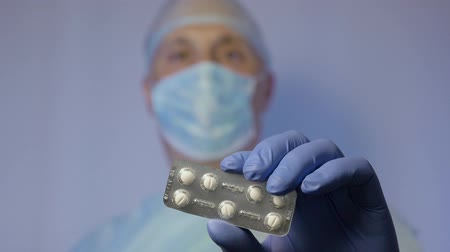 antimicrobial : A doctor surgeon shows the tablets in the package that need to take to a patient after surgery.