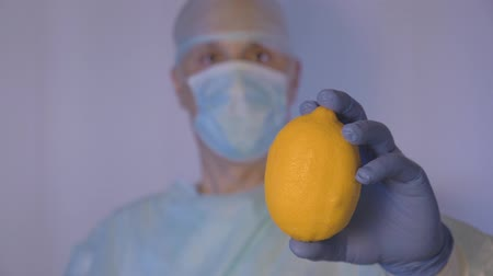 dietético : Doctor demonstrates lemon. And shows by gesture that this vitamin is very useful for your health. This is a natural remedy for colds.