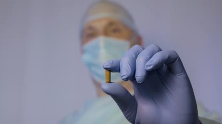 antimicrobial : A doctor surgeon shows the pill brown color that need to take to a patient after surgery.