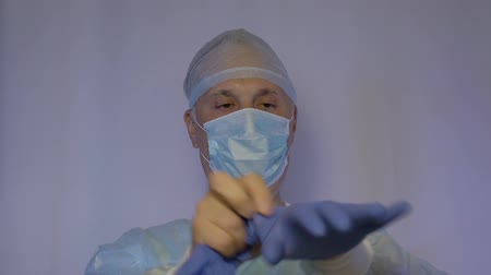 antimicrobial : Male doctor putting on medical disposable gloves. He is preparing for surgery Stock Footage