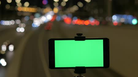 blurred lights : A smartphone with a green screen is fixed over the road. Against the background of the beautiful traffic lights of cars. Stock Footage