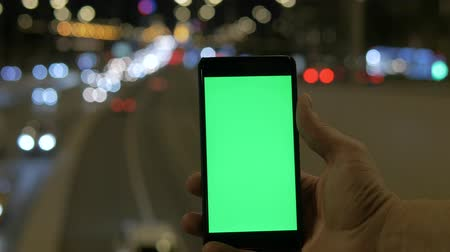 bulanık : A mans hand holds a smartphone with a green screen, against a background of motion blurred car lights. Stok Video