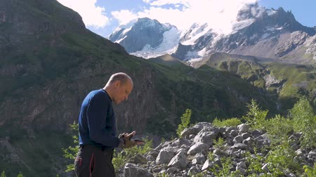 dağcı : A man stands in front of the mountain peaks and points to them with his hand. Stok Video