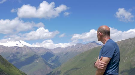 climber rock : A traveler stands high in the mountains and looks at the top of Elbrus