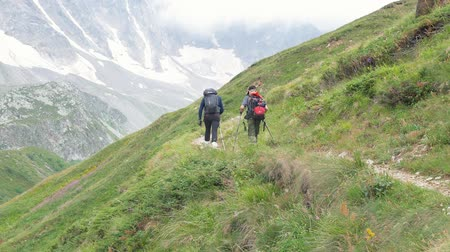 монтаж : Father and son go along the mountain path. They travel in the mountains of the Caucasus with backpacks behind their shoulders.