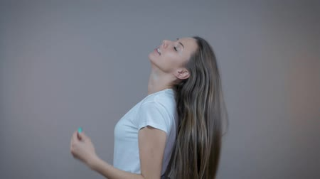yelek : A young sports model demonstrates her long hair, Im in the studio on a gray background.