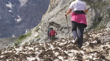 prozkoumat : A family of three people walks along the snowfield. They travel on foot along mountain paths.