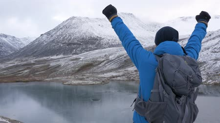 climbed : A man climbed high in the mountains, he rejoices and celebrates his victory, raises his hands up In front of him are beautiful mountains and a lake.