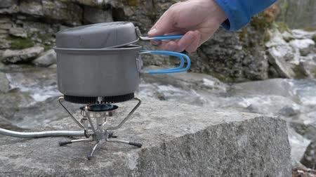 konvice : In the hike cook food on a portable gas burner. Close-up. On the bank of a mountain river.