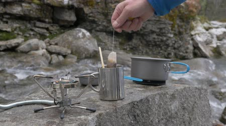 konvice : Close-up, portable gas burner, on which food is prepared during a hike. The flame is lit on it. She stands on the banks of a mountain river.