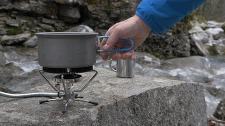 кемпинг : On a portable gas burner man puts a pot of water to cook dinner Close-up. On the bank of a mountain river. Стоковые видеозаписи