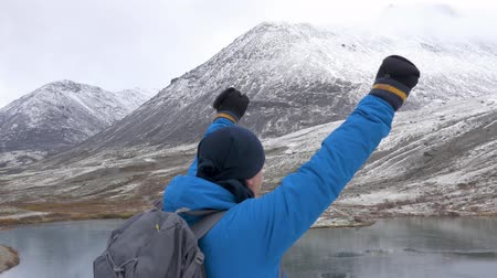 climbed : A man climbed high in the mountains, he rejoices and celebrates his victory, raises his hands up In front of him are beautiful mountains and a lake. close up