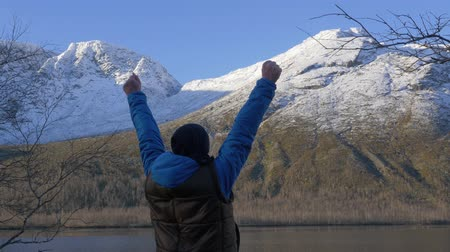 удачливый : A man, a middle-aged athlete, meets the dawn in the mountains. He raises his hands up, rejoices at the new day. All perfectly He admires the reflection of the sun and the mountains in the lake.