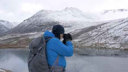 extreme weather : Sports man - photographer, traveling in the mountains with a backpack. He photographs beautiful landscapes on camera.