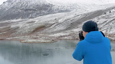 sorte : A man stands on a high point in the mountains and admires a beautiful view. There are peaks around it and a beautiful lake below. He photographs landscapes on the camera
