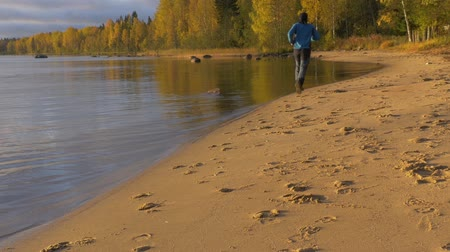 пробуждение : A man runs along the sandy beach. Early in the morning at dawn. He plays sports and leads a healthy life.