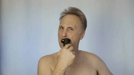 shaver : A man shaves with an electric razor. In the morning in front of the mirror. He looks after his appearance.