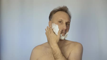 shaving foam : A man smears his face with special shaving foam. He is going to use a razor.