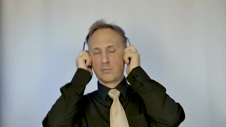 earpiece : A man in a shirt and tie, listening to music through headphones. He moves in rhythm.