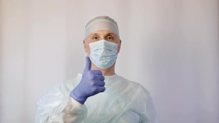 eye mask : The doctor is a surgeon in a medical mask, shows the patient that everything is fine He lifts his thumb up and is positively tuned Stock Footage