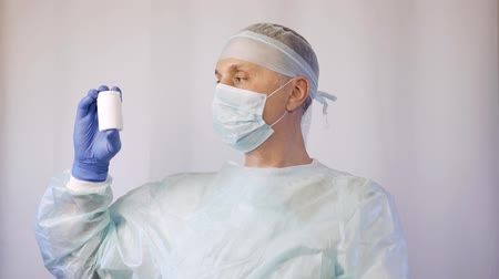 antimicrobial : A doctor in a medical mask and gloves shows his hand on a tube of pills. The patient must take medicine.