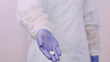 antimicrobial : Hands doctor in gloves, close-up. He holds out a pill in his palm. Stock Footage