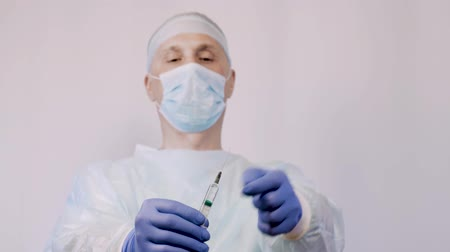 dose de : The doctor is a surgeon, holding a syringe with the vaccine. He is preparing to give the patient an injection. Remove extra air from the needle. Stock Footage