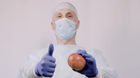 dietético : The doctor points to an apple. And the gesture makes it clear that these are the best natural vitamins for health.