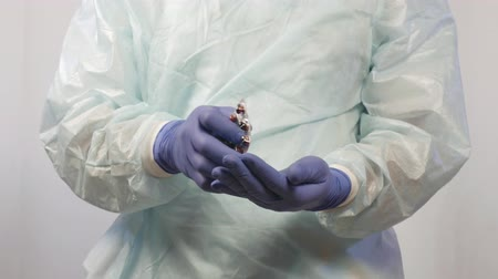 antimicrobial : The hands of a male doctor in medical gloves remove the tablets from the package, which must be taken to the patient. Stock Footage