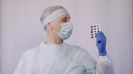 cápsula : A doctor surgeon shows the tablets in the package that need to take to a patient after surgery.