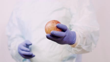 antimicrobial : The doctor holds out an apple to the patient. Hands in medical gloves, closeup.