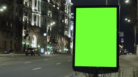 poste de sinalização : Billboard with a green screen, located on a busy street. Cars move in the evening. Vídeos