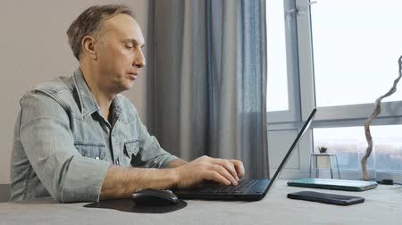 vstoupit : A middle aged man working on a laptop. Freelancer works at home.