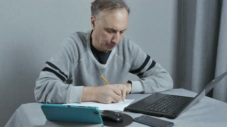 рабочий стол : A man writes a work plan. He works at home remotely. Using modern technology. Стоковые видеозаписи